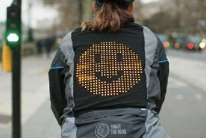 The jacket displays emojis on an LED panel.