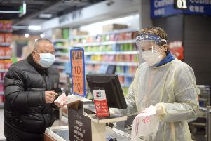 A staff member wearing a protective mask and suit works at a supermarket in Wuhan, the epicentre of the outbreak of a novel coronavirus, in China's central Hubei province (Picture: STR/AFP via Getty Images)