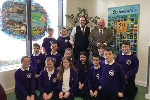 Philip Tibbetts (Honorary Vexillologist with the Court of Lord Lyon) and Andrew Walker (Competiton Steering Group Co-ordinator) with pupils from the North Uist primary school Sgoil Uibhist a Tuath.