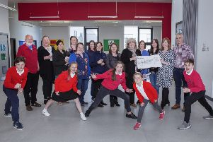 Christina Smith from Point and Sandwick Trust (holding cheque) hands the first instalment to Anne Macphail of Sgoil an Rubha, cheered on by some of the P7 parents and Sgoil an Rubha pupils, as well as other representatives from Point and Sandwick Trust. Picture by Sandie Maciver of SandiePhotos.