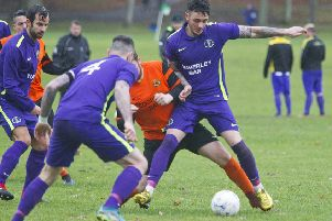TIght, physical derby action in demanding conditions between Hawick Waverley, in purple, and Hawick United (picture by Bill McBurnie).