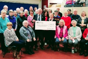 Henry Douglas receives a cheque for £1,000 on behalf of the trustees of the My Name'5 Doddie Foundation from Marion Dodd, musical director of the Roxburgh Singers, following their recent performance of Handel's Messiah in Melrose Parish Church.