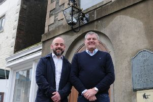 Stuart Davidson and David Heard with the restored lamp above the Town Hall front door.