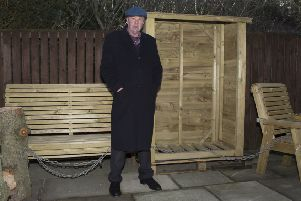 Daniel Howard with his wooden furniture.