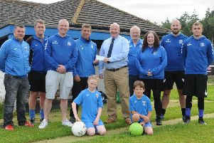 Deacon of The Selkirk Incorporation of Hammermen, Alan Tough, hands over a �500 cheque at Yarrow Park to Ian Stephen, chairman of Selkirk Community Football Club, with members of the Selkirk Victoria and Junior football teams (picture by Grant Kinghorn)