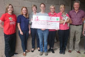 Borders Pet Rescue manager Lee-Ann Lackie (fourth from left) accepts the bumper cheque from Pets at Home's Catriona Curtis (second from left), watched by staff and volunteers from both organisations.