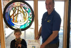 Lucy Jessop, of Lauder primary school's gardening club, is this year's Lauder in Bloom 'Gardener of the Year'. Pictured are Lucy  and Alistair Smith, chair of Lauder in Bloom